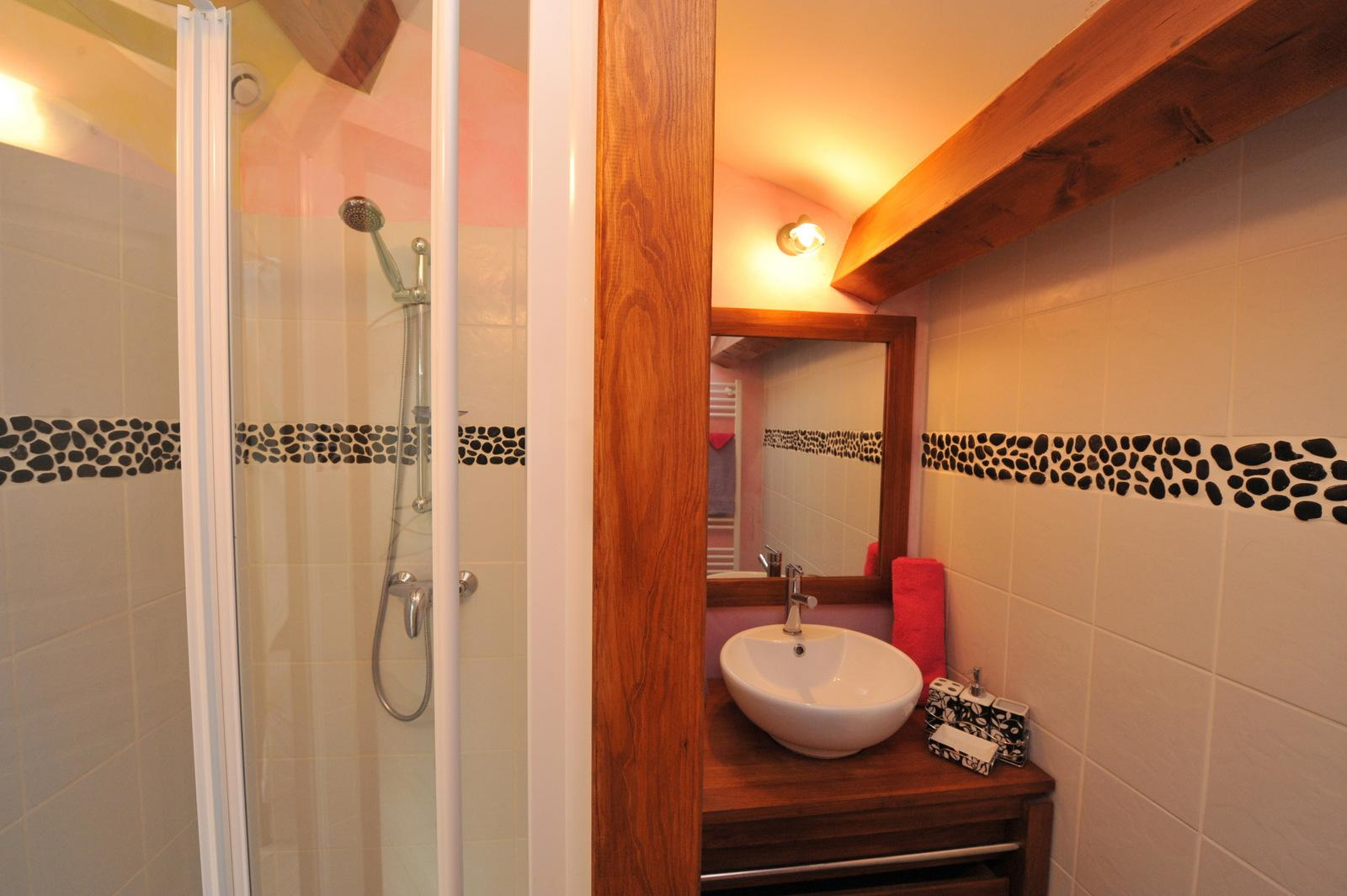 Private bathroom for that romantic guest room with shower and wall frieze pebbles bowl sink set on a wooden slats plan